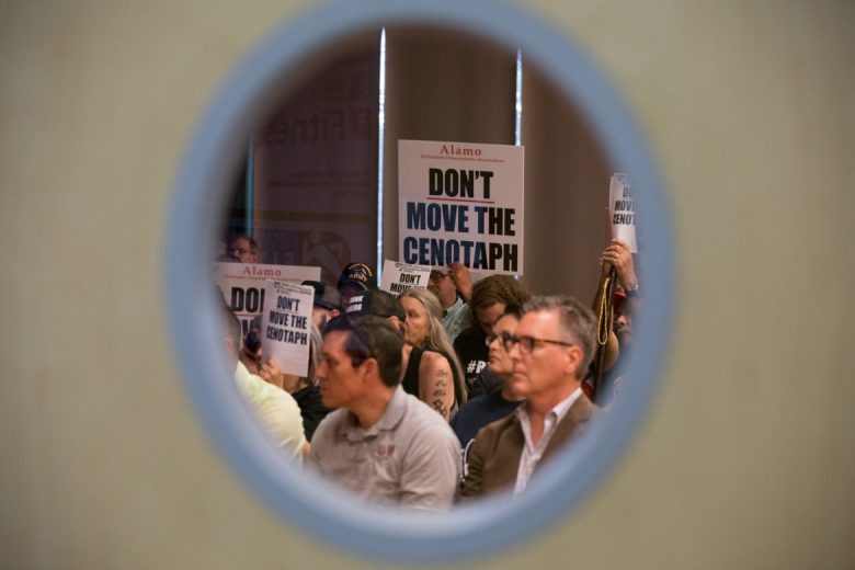 During a public input session on the Alamo master plan attendees hold signs protesting the moving of the cenotaph.