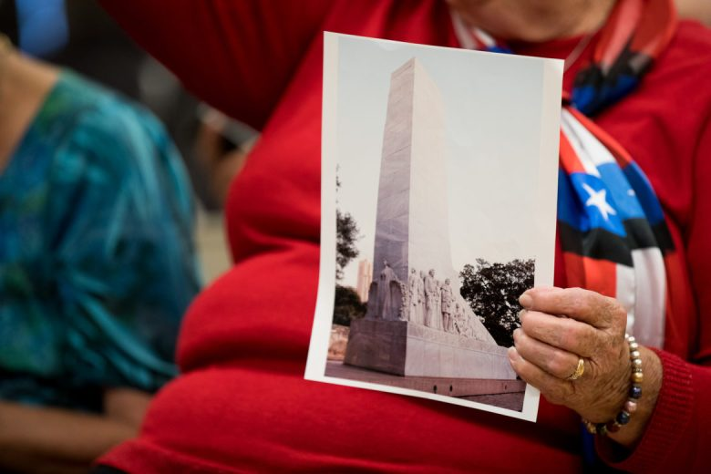 An attendee at a recent Alamo public input meeting holds up a photograph of the Alamo Cenotaph.