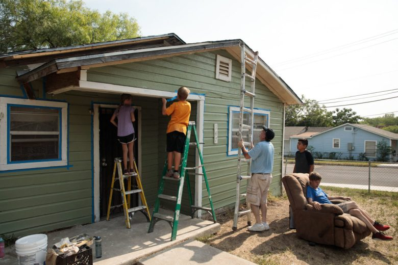 Volunteers from BluePrint Ministries tape off sections of Debra's house in preparation of paint.