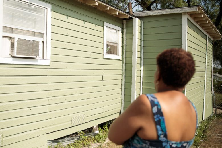 After replaced siding, a new roof, and a fresh coat of paint, Debra Clay gazes at her repairing home.