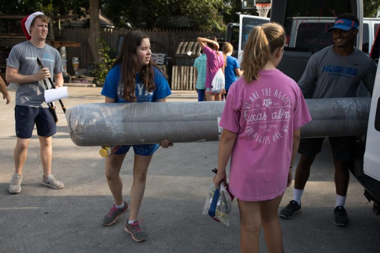 Blueprint Ministies volunteers Kristin, 14, and Gabe Byrd load carpeting into one of the many team vans.