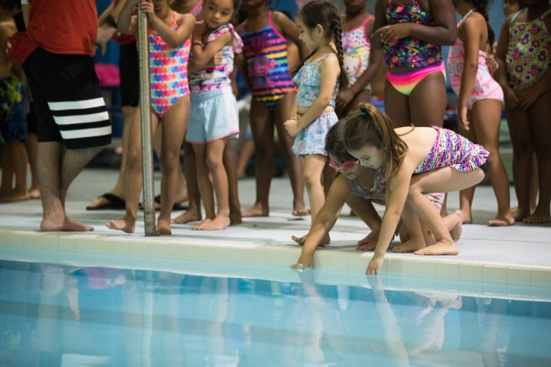 Children dip their hands into the pool before getting in on the first day of training.