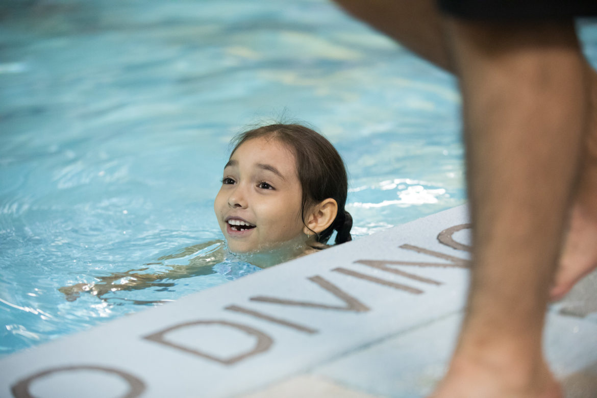 A child smiles as she swims across the pool with encouragement from a lifeguard.