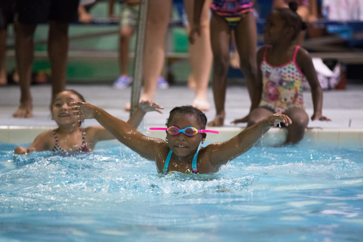 A child jumps into the pool during her first swim of the camp.