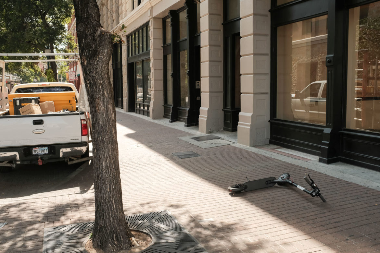A bird scooter lays on the sidewalk along East Houston Street.
