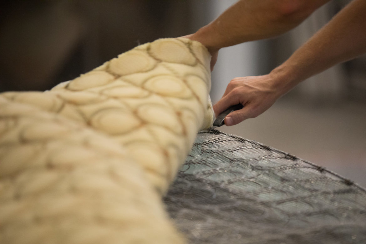 Re-Mat Founder and Director Christopher Moken disassembles a twin sized mattress to recycle it's materials.