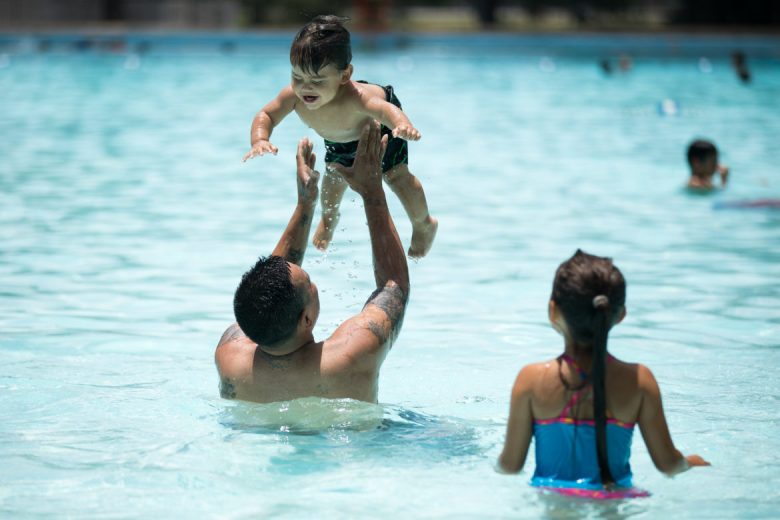 Rey Salazar with his son Rey, one year, and his niece Annabella 7, plays in the water at Woodlawn Lake Pool.