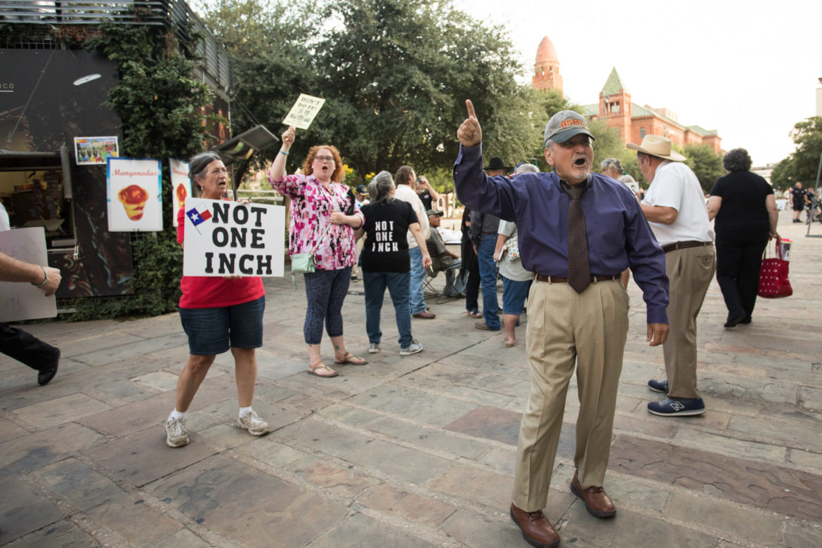"""Protesters yell """"not one inch!"""" outside of City Council Chambers after the proposed design for Alamo Plaza's redevelopment was approved."""