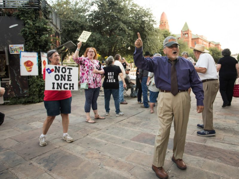 "Protesters yell ""not one inch!"" outside of City Council Chambers after the proposed design for Alamo Plaza's redevelopment was approved."