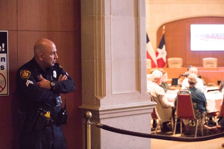 A police officer watches the proceedings of the presentation and series of votes.