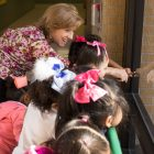 Carvajal Early Childhood Education Center teacher Andrea Greimel shows her students a feather outside.