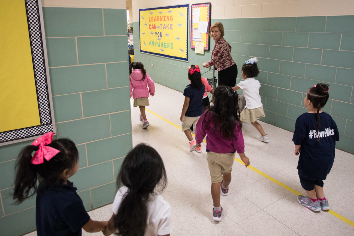 Carvajal Early Childhood Education Center teacher Andrea Greimel walks her students back to the classroom from the restroom.
