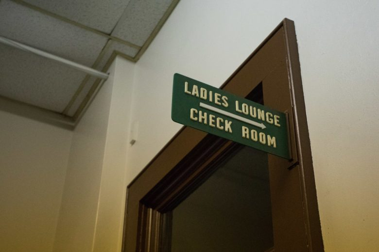A vintage sign points to what used to be the ladies lounge and check room.