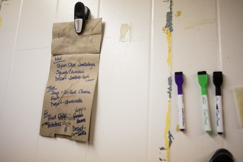 A list of the food being served is written on a paper bag and hung on the side of the refrigerator.
