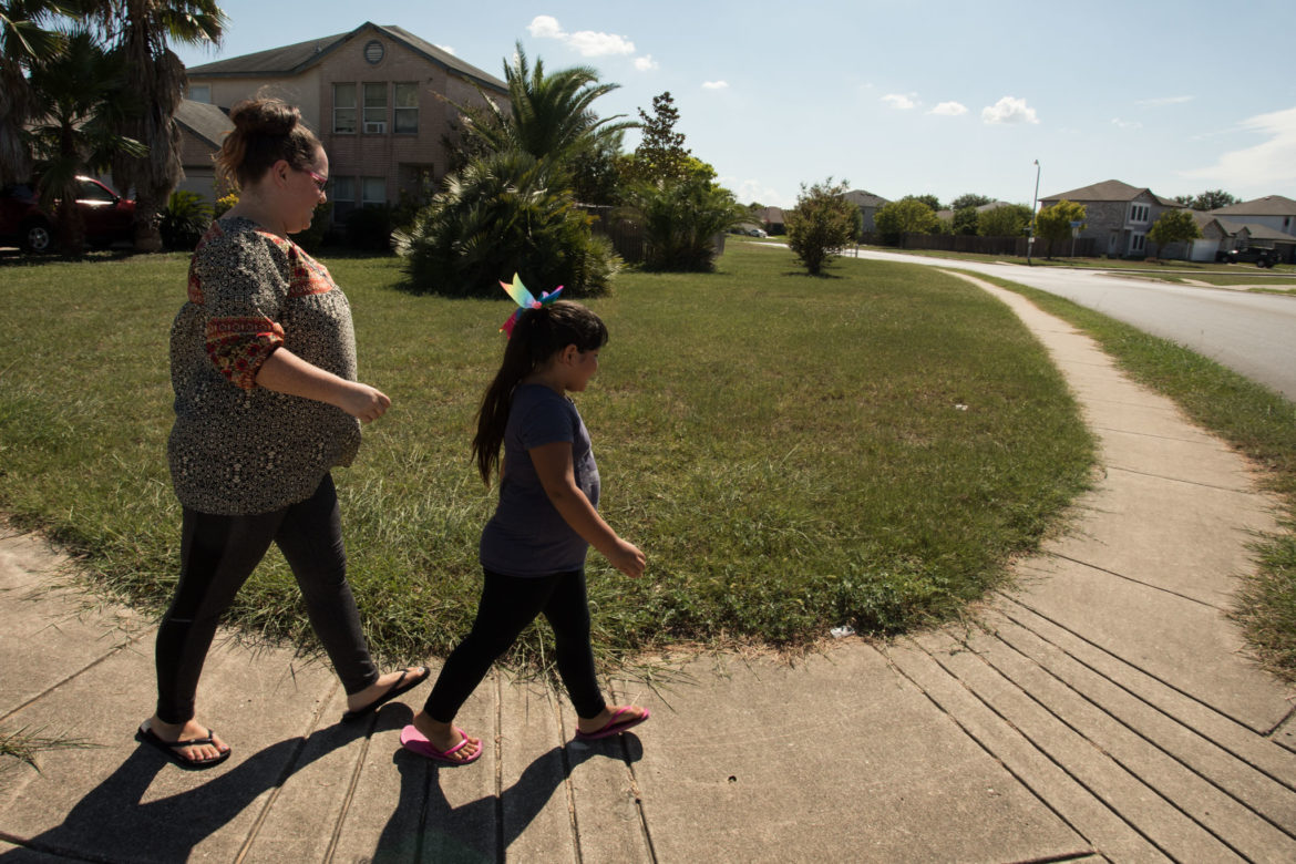 (From left) Meghan Fridley and her daughter Ambrosia, 7, walk the new route to where the school bus will pick up Ambrosia for school.