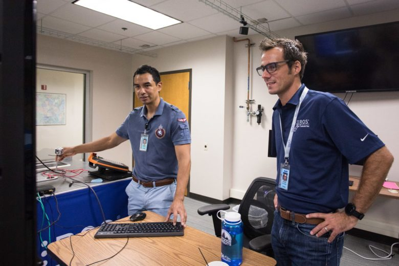 (From left) Jorge Nicho, mechanical engineer, and Matt Robinson, program manager, discuss a robot in the Collaborative Robotics Laboratory at Southwest Research Institute.
