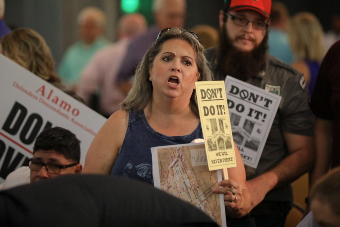"""Krystal Ross speaks in opposition to the proposal as she holds a sign in opposition of moving the Alamo Cenotaph, """"They don't want it (cenotaph) where it belongs because of the history it represents"""""""