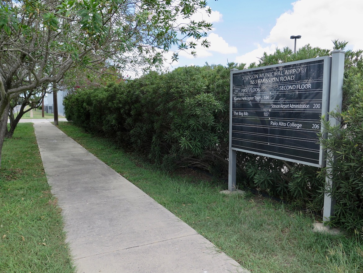 A directory sign for Stinson Airport is located beyond a sidewalk across Mission Road from the airport.
