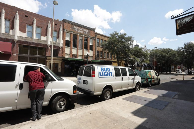 Commercial vehicles line up along the side of Losoya Street.