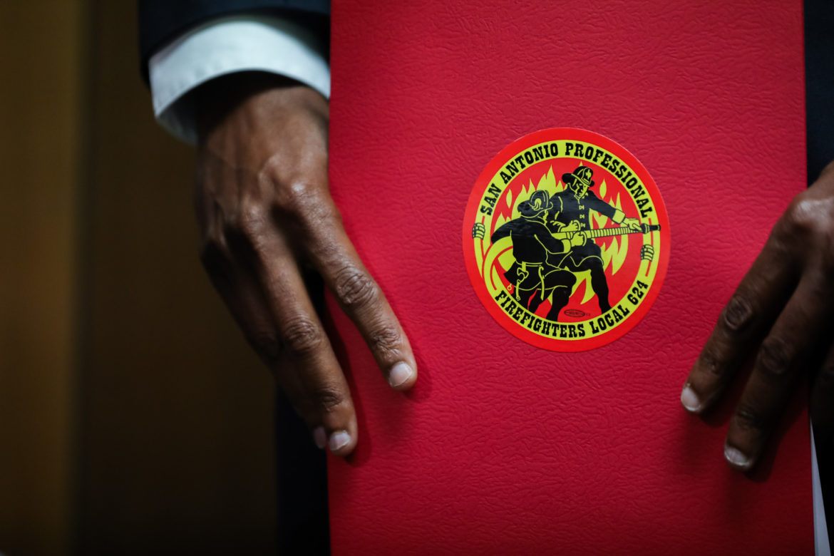 San Antonio Professional Firefighters Association President Chris Steele holds a folder with his association's seal.
