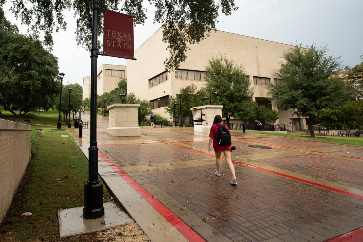 A student walks through the Texas State University campus.