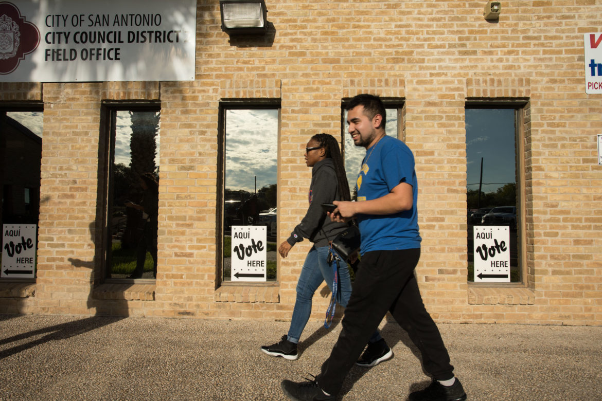 IDEA Carver teacher Brittany Hibbert (left) accompanies IDEA Carver senior Noah Martinez, 19, as he votes for the first time at the Claude Black Community Center polling site.