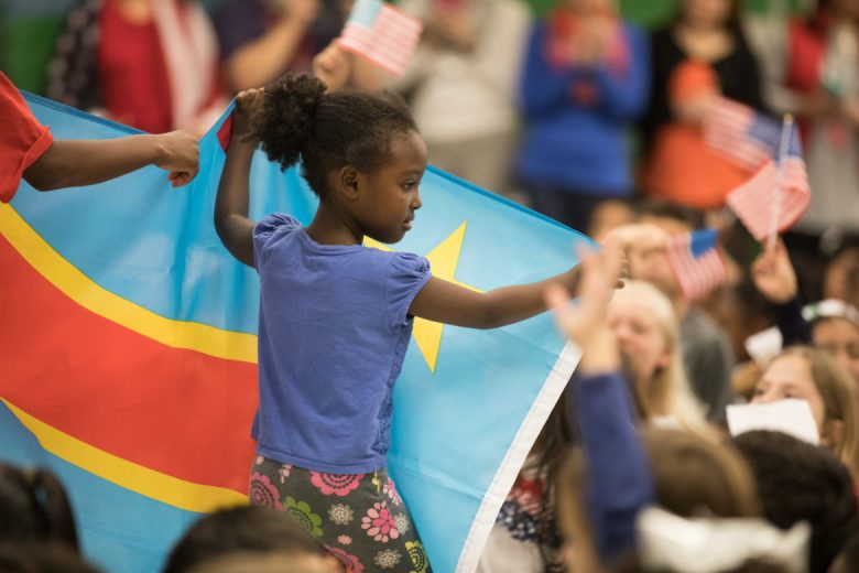 A girl carries a flag from Congo through the crowd.