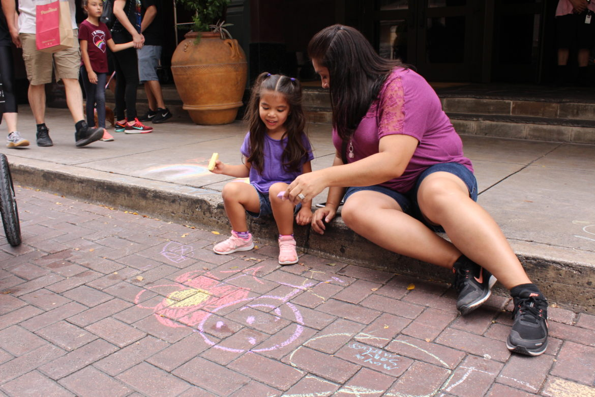 Alyssa Hermosa, 4, uses chalk to draw on Houston Street with her mom, Sandra Hermosa, at Artpace's 15th annual Chalk It Up event.