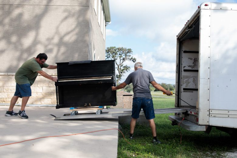 An old piano from Gateway Fellowship of Bandera church is wheeled onto Neil's box truck.