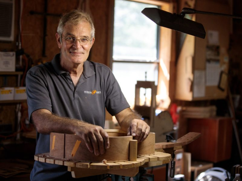Neil Peterson stands over one of his handmade acoustic guitars in his Bandera wood shop.