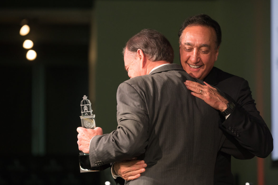 Former San Antonio Mayor and Secretary of Housing and Urban Development Henry Cisneros hugs Texas A&M Chancellor John Sharp after being introduced.