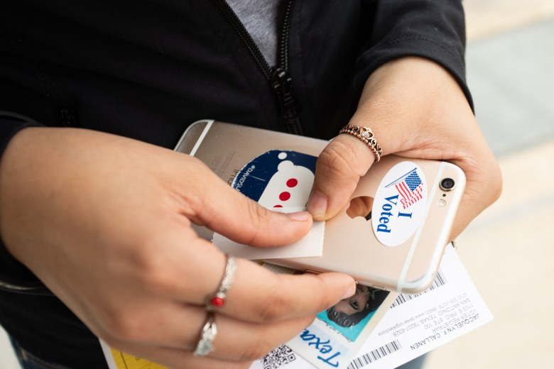 "Travis Early College High School senior Brenda Gomez puts her ""I Voted"" sticker on the back of her phone after voting for the first time."