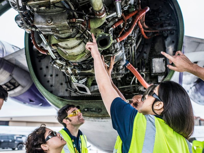 Students inspect the engine of a Boeing 727 aircraft at the College of Aeronautics.