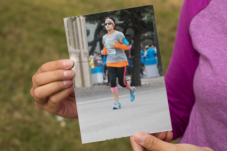Analicia Martinez-Foley holds a photo of her first marathon run.