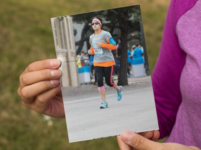 Analicia Martinez-Foley holds a photo of her first marathon run.