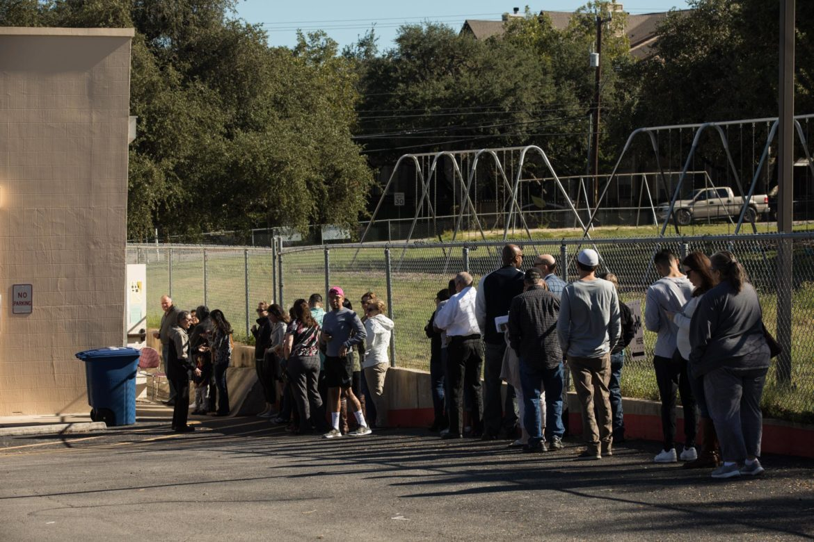 A long line forms along the fence outside of Cody Library during early voting.
