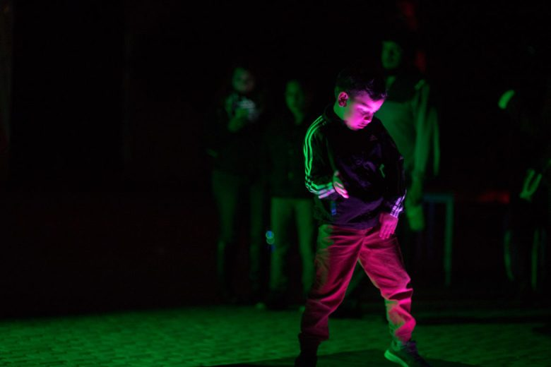 A young boy dances on an illuminated dance pad near the main stage.
