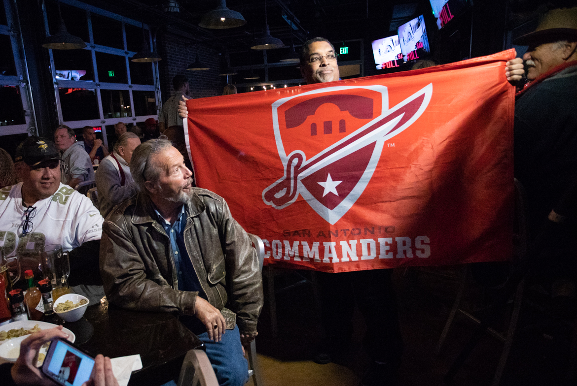San Antonio Commanders season ticket holder Stephen Canto waves a flag during the watch party.