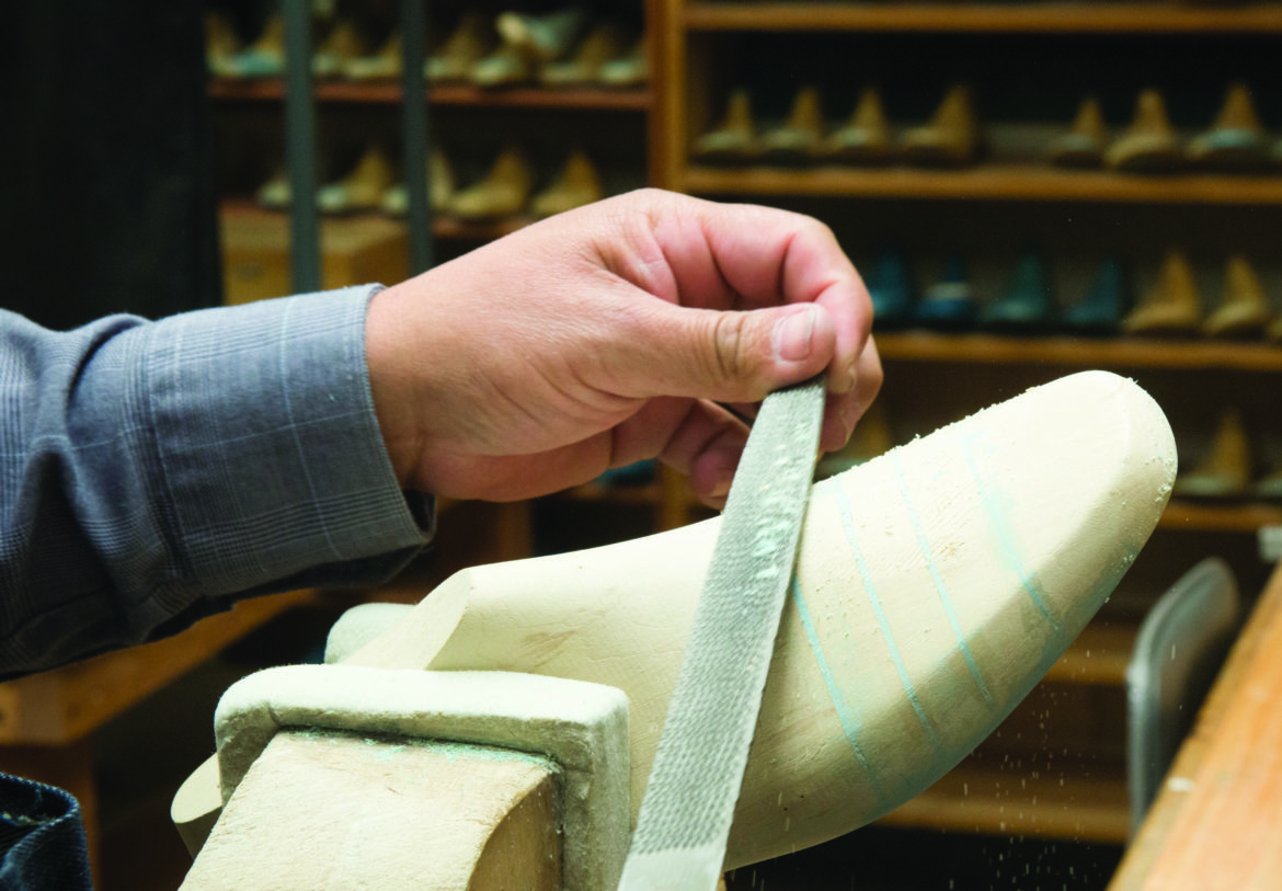 A shoe last is hand carved by a SAS employee.