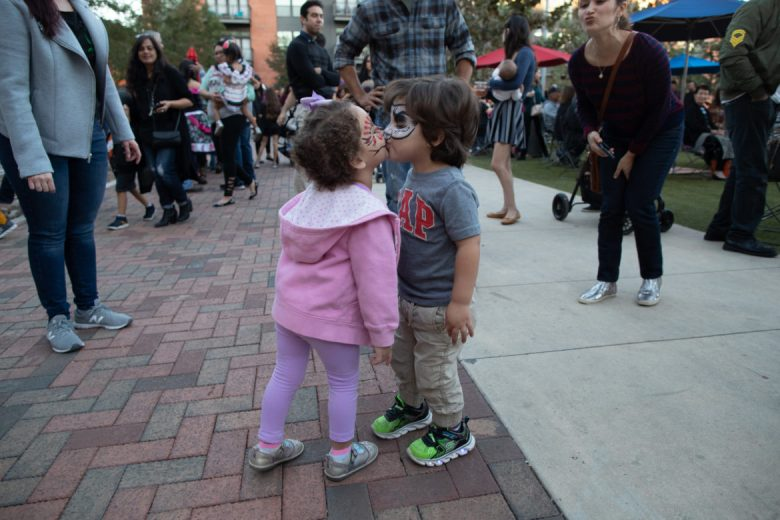 Lionel Briseño, 3, tries to kiss a girl at the Pearl Brewery during Dia De Los Muertos.