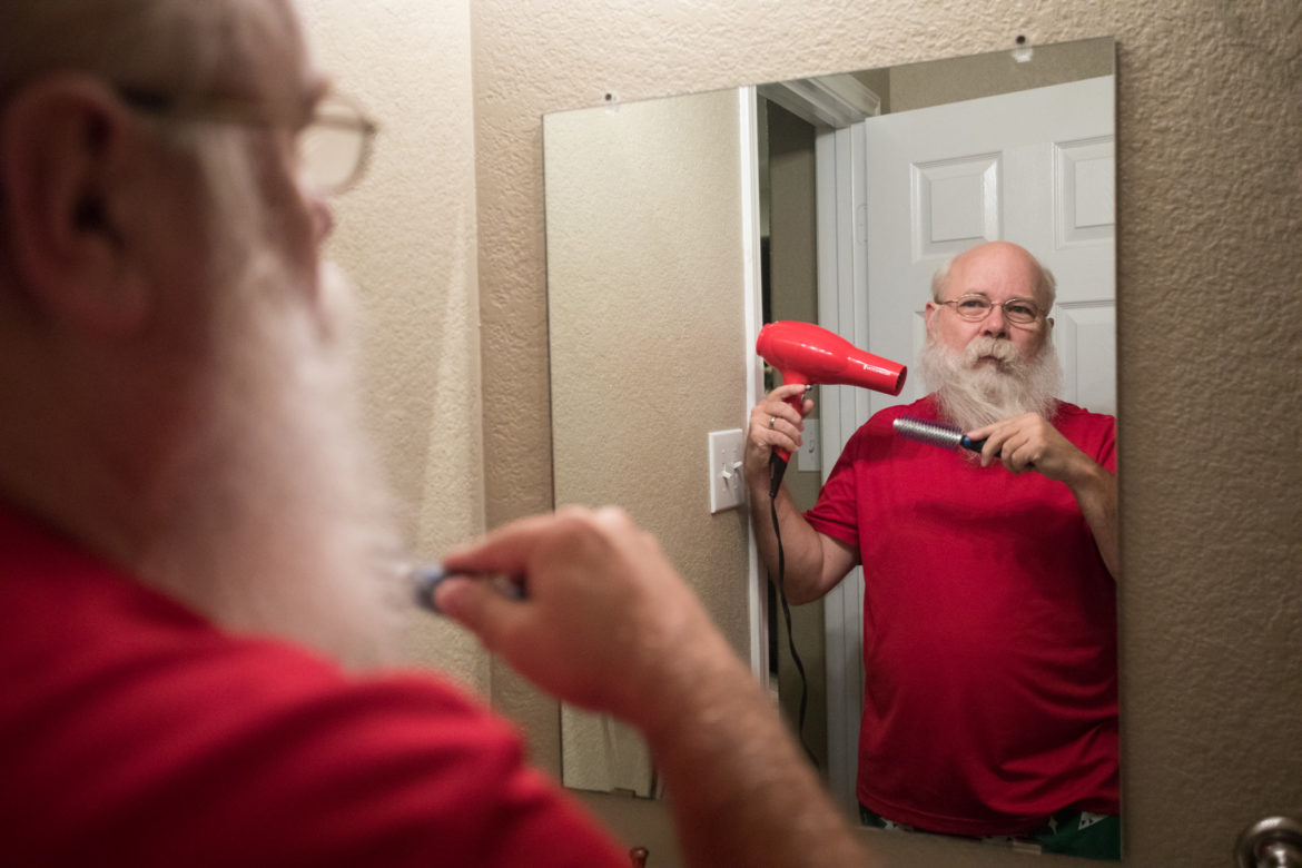 Mark Hotchkiss prepares for a day dressed as Santa by blow-drying his beard.
