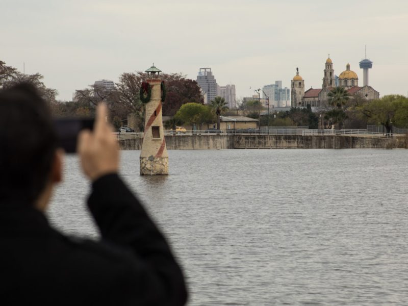 A man takes a photograph of the downtown skyline from Woodlawn Lake Park.