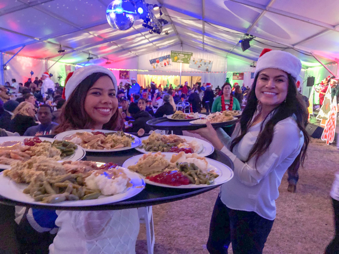 Volunteers Kassandra Gonzales (l) and Angela Ramirez (r) on their way to hungry diners at the 2018 Ho Ho Hope for the Holidays dinner at the Haven for Hope on Dec. 6.