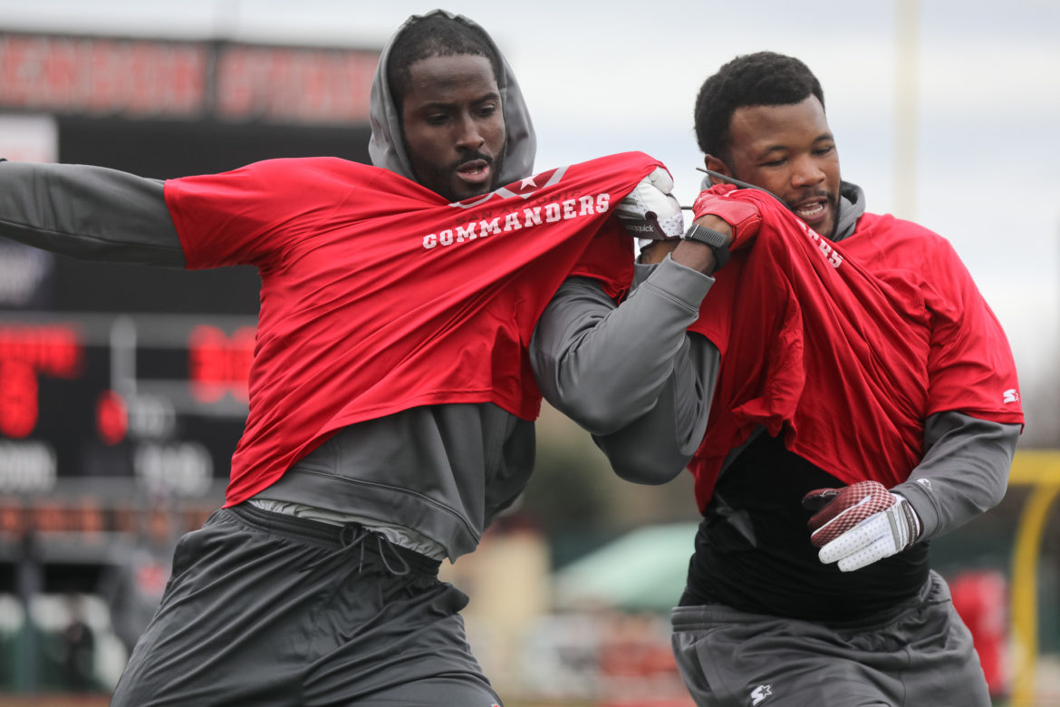 Jevoni Robinson (left) works on a blocking repetition with teammates.