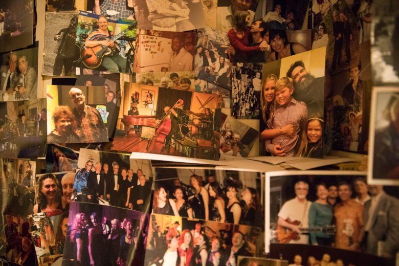 Photographs from past parties and friends of One Minute to Midnight line a wall in the kitchen.