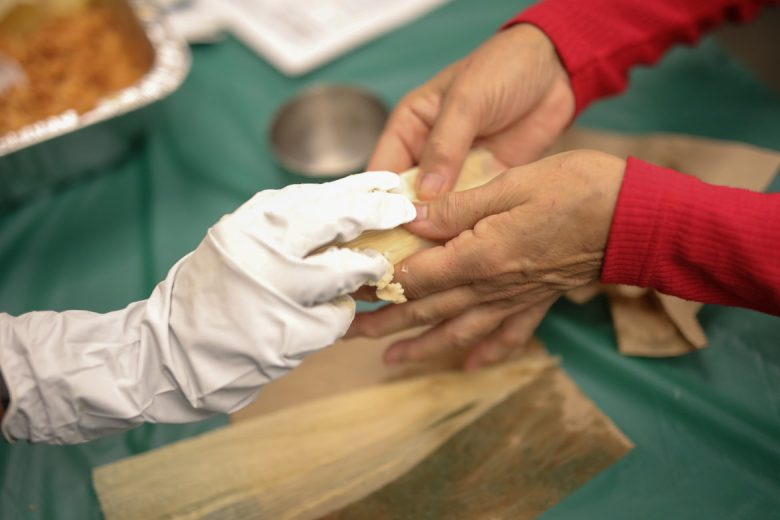 A tamale is finished by pressing together the ends of the cornhusk after a filling has been spread.