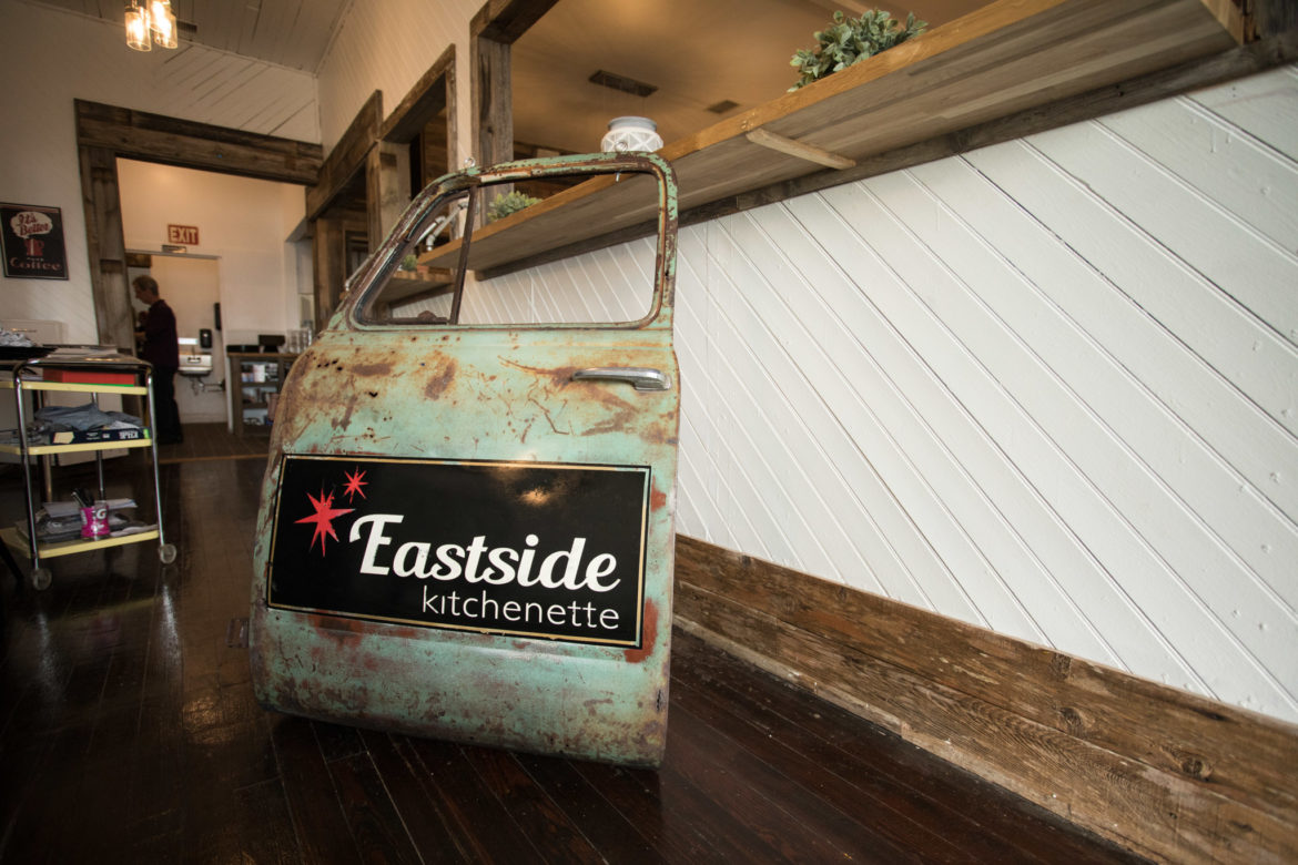 The sign of Eastside Kitchenette waits in the lobby to be hung outside.