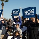 Supporters for the re-election of Mayor Ron Nirenberg hold up signs during his campaign announcement.