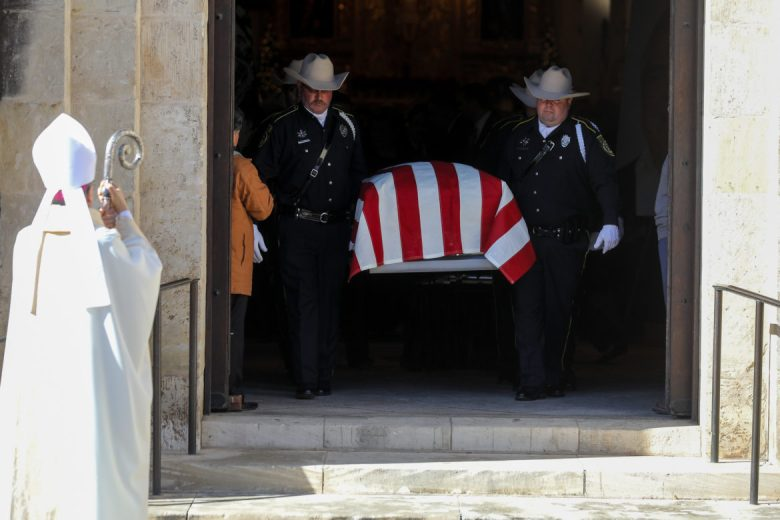 Bexar County Sheriff Deputies carry the casket of Paul Elizondo following the funeral service as Archbishop Gustavo García-Siller looks on.
