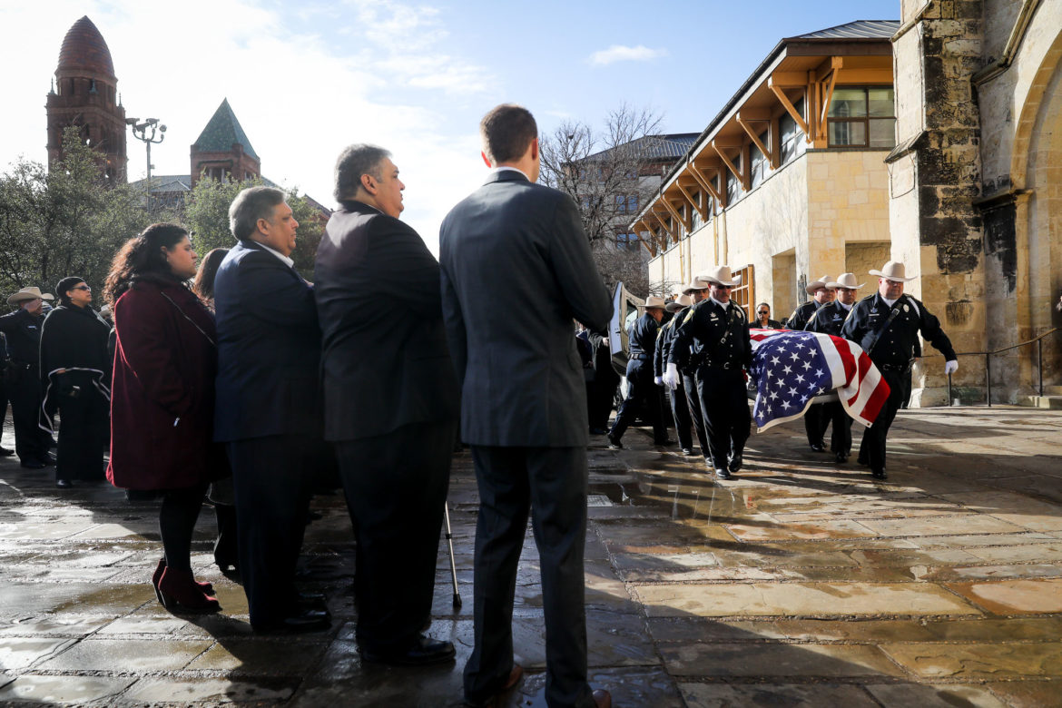 Bexar County Sheriff Deputies carry the casket of Paul Elizondo as family (left) looks on.